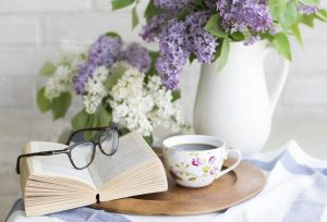 glass on top of book next to vase of flowers on front ot coffee cup