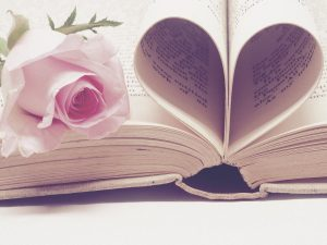 a rose laying on a book next to pages forming a heart